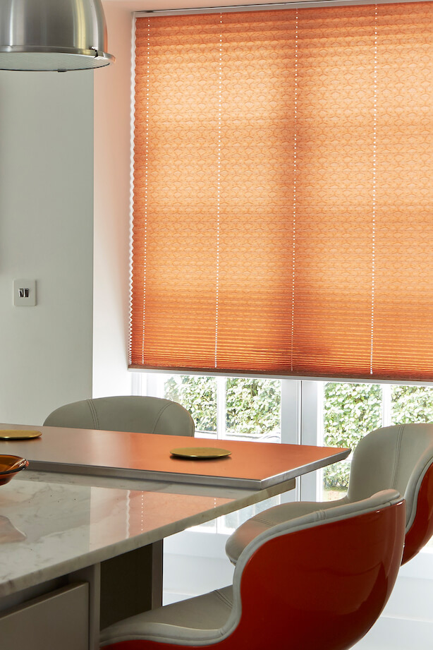 Dining room with a table in front of a large window with a Hillarys orange Pleated blind in Crush Nectarine fabric
