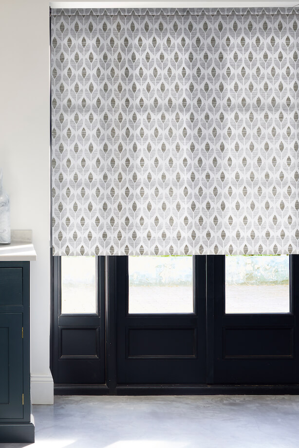 Large navy blue French doors with a roller blind half drawn down. The Hillarys Roller blind is in Petula Smoke patterned fabric