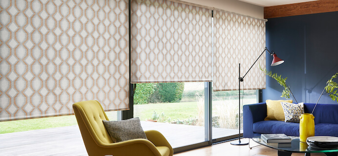 Bi-fold floor to ceiling doors in a living room fitted with Hillarys Roller blinds in Brindle Spice fabric