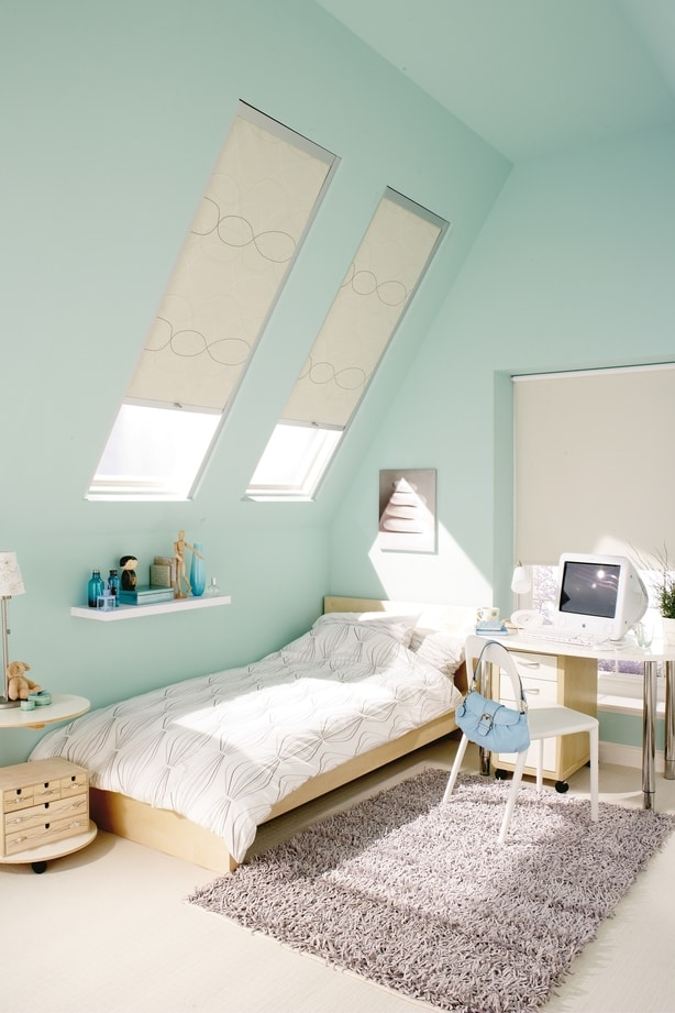 An skylight window in a bedroom with a white Hillarys Skylight Blind fitted to the window