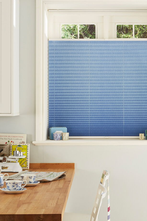 A kitchen window with a Hillarys pleated Top Down, Bottom Up blind in blue Salerno Azure fabric